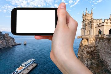 tourist photographs pier and Swallow's Nest Castle