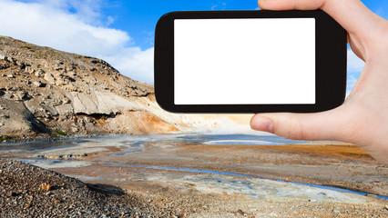tourist photographs mud pot crater in Krysuvik