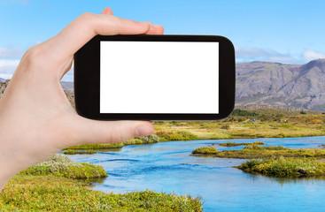 tourist photographs Oxara river in Thingvellir