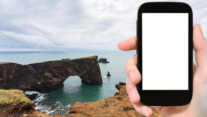 tourist photographs Dyrholaey cliff in Iceland