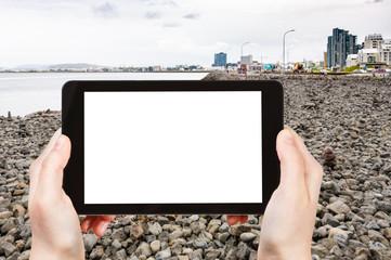 tourist photographs stone beach in Reykjavik city