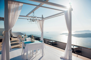 White arch for a wedding ceremony in the open air with lanterns and a platform with white furniture on the background of the sea, islands and blue sky on the island of Santorini