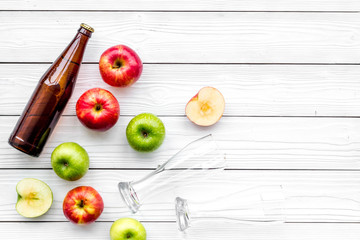 Apple cider. Low-alcoholic beveradge in dark bottle near beer glasses and fresh apples on white wooden background top view copy space