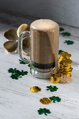St Patrick's day dark beer with foam head surrounded by gold coins and four leaf clovers on white background
