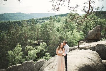 Keuken foto achterwand Olijf Wedding couple in love kissing and hugging near rocks on beautiful landscape