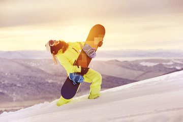 Happy lady snowboarder having fun with snowboard
