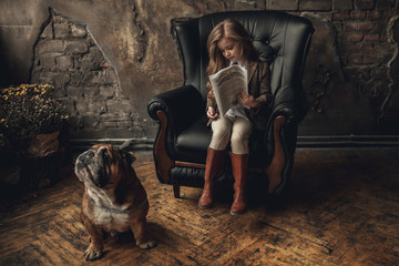 Child girl in image of Sherlock Holmes sits in armchair and reads newspaper next to English bulldog on background of old interior.