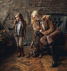 Child girl with woman in image of Sherlock Holmes read newspaper next to English bulldog on background of armchair and old interior.