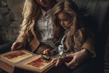 Child girl with woman in image of Sherlock Holmes sits and looks photoalbum with magnifier on background of old interior.