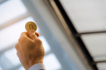 close up business man hand holding golden Bitcoin on city background, digital technology, virtual currency, financial, investment, saving money, payment and shopping online concept, sunlight effect