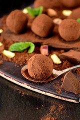 Chocolate truffles covered with cacao powder, pistachio nuts, chocolate and mint on a dark wooden board