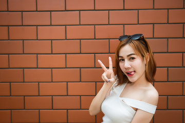 Portrait asian sexy hipster girl on brick wall background,fashion concept,thailand people