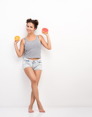 Cute young woman holds in her hands the orange and the grapefruit. Portrait in full growth on a background of white walls