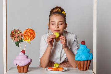 Beautiful teenage model girl in pink tutu or tulle skirts with macaroons, lollipops and artificial fancy cakes in studio on white background