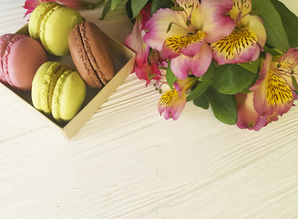 macaron in a box on a white wooden background, alstroemeria flowe