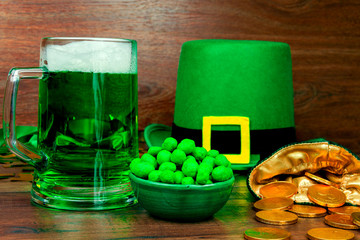 Saint Patrick's Day. Green glass pint of beer, green snacks cookies sweets,  green hat of leprechaun, green three petal clover and gold coins on wooden background