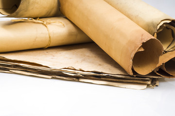 Scrolls of parchment on a background of sheets of old parchment on a white background