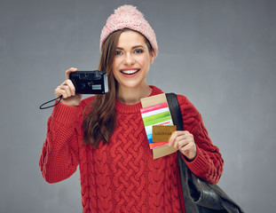 Happy woman dressed red knitted sweater holding camera, credit c