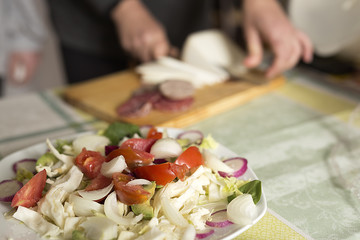 Salad in the foreground and the background a person working out of focus