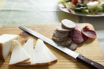 Cheese and sausages cut on a cutting board. Hoarizontal shot