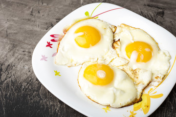 Fried eggs on a plate. Dark background. Hot appetizing dish. Copy space 1
