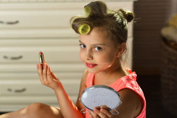 Little girl holds bright lipstick and mirror sitting in room