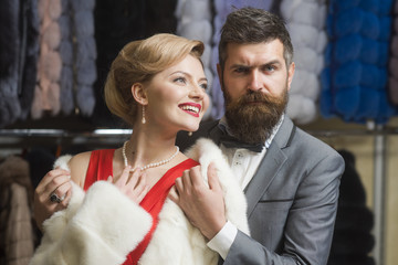 Guy with beard and woman buy furry coat.