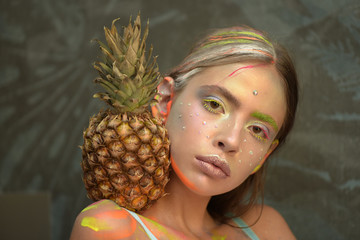 Young girl poses with pineapple fruit on shoulder