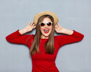 Young woman dressed in hipster style with hat and sunglasses.