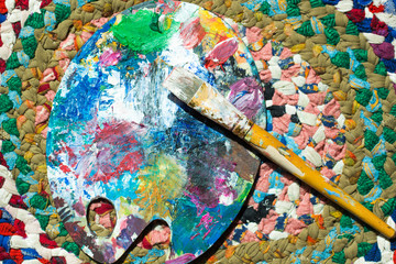 Palette and brush, colorful paints, powder on abstract background