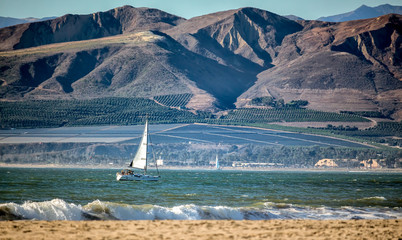 Sailboat crusing off shore from beach and mountains