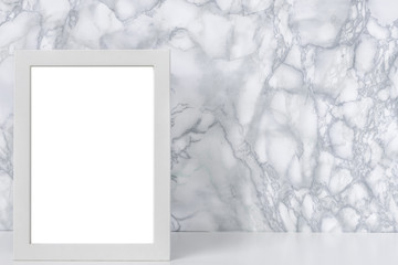 White desk, marble gray wall and white vertical empty frame