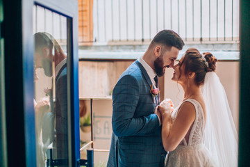 beautiful and young newlyweds couple  in a cozy urban space cafe or restaurant. Bride and groom posing and hug each other.