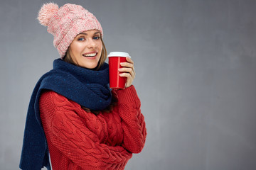 Smiling woman wearing warm clothes with winter hat holding red c