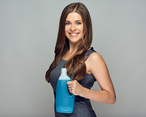 Smiling woman holding cleaner product in bottle