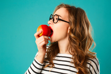 Portrait of young beautiful blond woman in round black glasses eating red apple over blue background