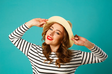 Portrait of young beautiful smiley blond woman in hat over blue background