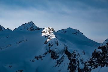 Ausblick auf die Berge mit Licht auf dem Grad im Winter