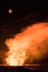 Moon eclipsing over volcano crater