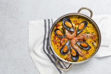 Traditional rice in paella with fish and meat.