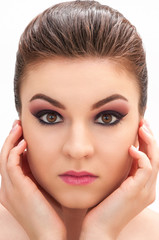 Close up shot of a young beautiful model with professional make up holding her face with her hands