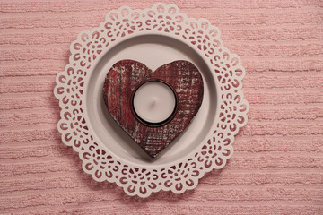 wooden heart decoration on a pink background