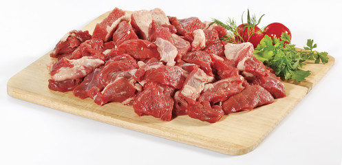 fresh raw red cubed meat chunk on wooden cut board isolated over white background