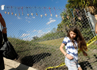 Young student walks under crosses for the victims of the Marjory Stoneman Douglas High School shooting hang on a fence in Parkland