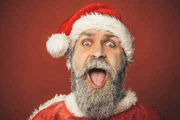 New Year, holidays, Christmas and people concept - cheerful and hilarious Santa Claus man in red traditional outfit isolated on red background. Merry Christmas and Happy New Year!