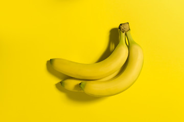 Three bananas on a yellow background.