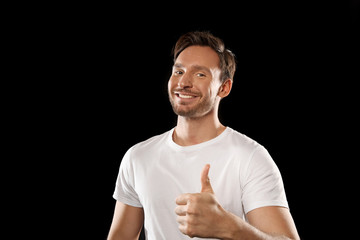 Handsome young man in a white t shirt isolated on a black background. Happy guy is smiling with his thumbs up
