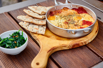 Scrambled eggs with tomatoes, cheese and spices in an aluminum frying pan with handles with homemade thin lavash and juicy greens on a wooden brown table. The photo was taken under natural light.