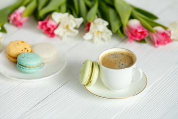 Coffee, pink and white tulips and macarons on the white wooden table