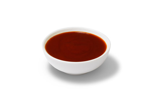 Red sauce in a gravy boat on white background